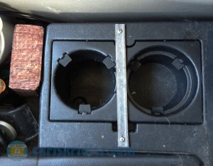 Here you can see the wood block that helps support the elbow of the pipe, the hole created by cutting off the bottom of the left cupholder, and the metal strip that holds the cupholder piece in place. Photo by Chris Kridler, ChrisKridler.com, SkyDiary.com